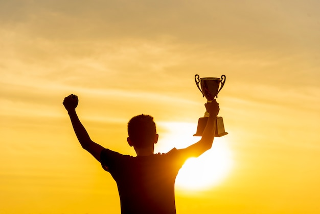 Silhouette of a winning man holding golden champion trophy cup prize.