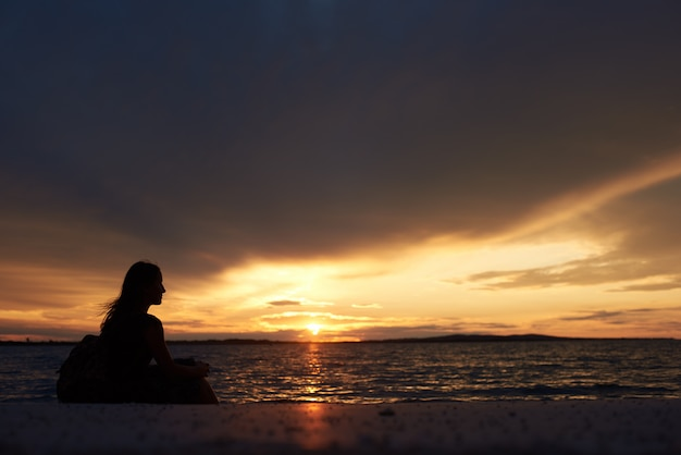 Silhouette of woman alone at water edge, enjoying beautiful seascape at sunset.