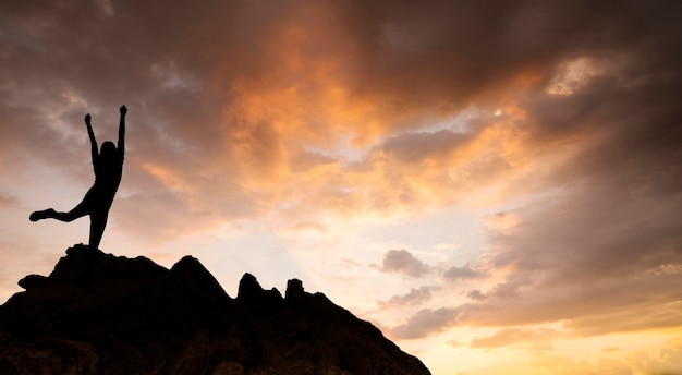 Silhouette of woman celebrating success standing on top mountain at sunrise.
