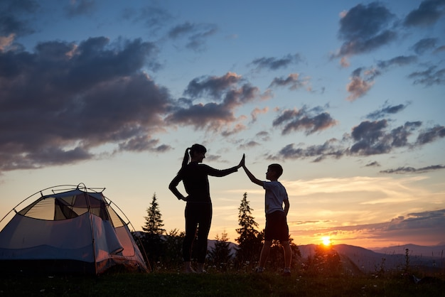 Silhouette of woman and child giving each other a high five near a camping at dawn on top of a mountain. a beautiful landscape of fir-trees and sun rising over the mountains and hills