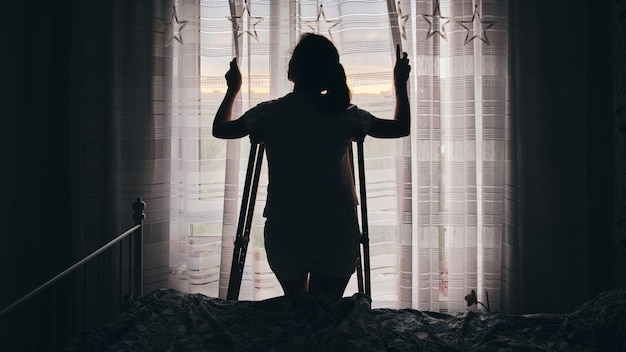 Silhouette of a woman on crutches by the window. rehabilitation after physical trauma.