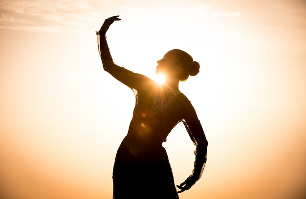 Silhouette of the woman dancing at sunrise