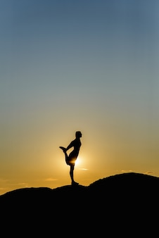 Silhouette of woman doing yoga on a sunset