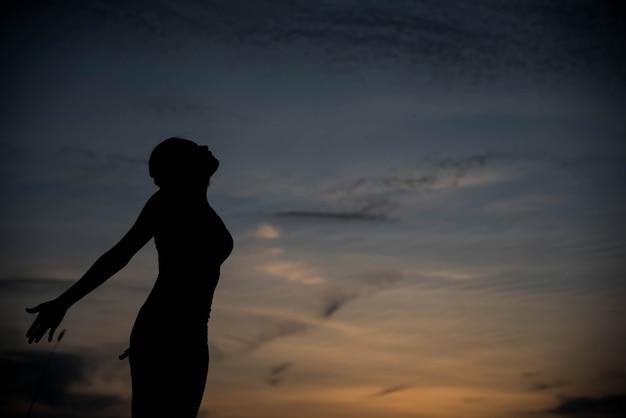 幸せと夕日のシルエットの女性