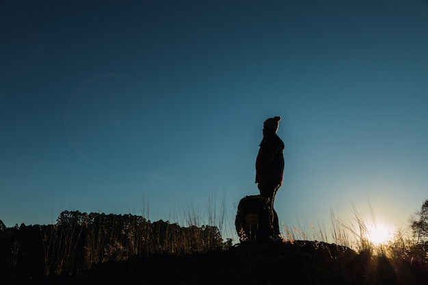 Silhouette of a woman hiker at the top of a hill.