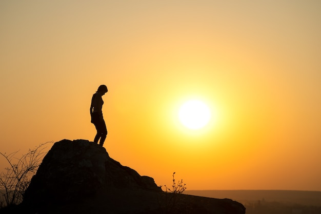 Silhouette of a woman hiker walking down a big stone at sunset in mountains. female tourist on high rock in evening nature. tourism, traveling and healthy lifestyle concept.