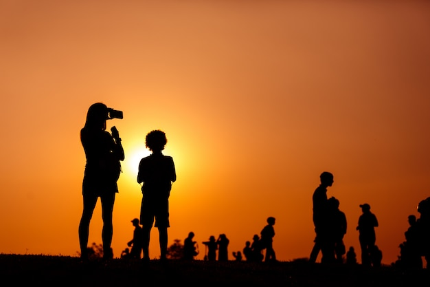Silhouette of a woman holding a smartphone taking pictures with child and crowd people