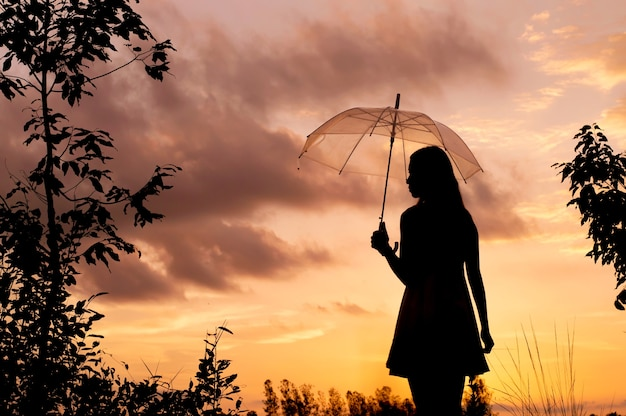Silhouette of woman holding a umbrella with sunset sky