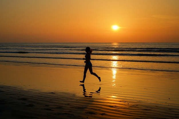 Silhouette of woman jogger running on sunset beach with reflection, fitness and sport concept