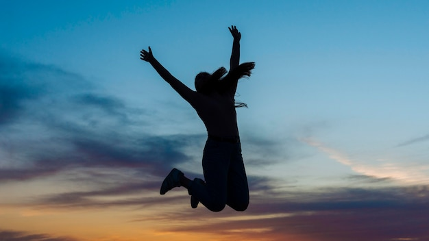 Silhouette of woman jumping in the air at sunset