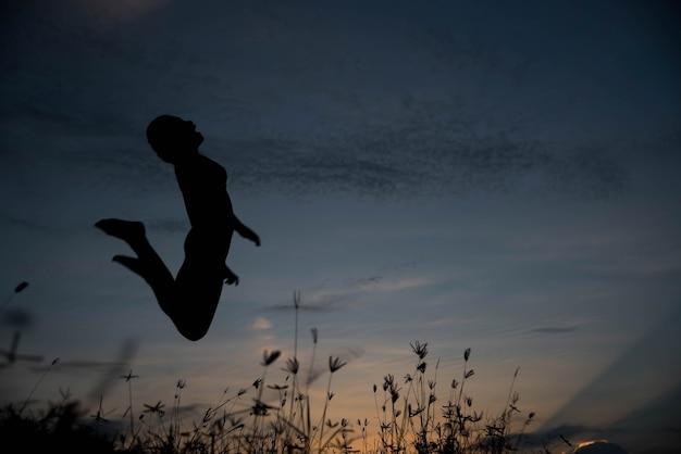 일몰에 점프하는 실루엣 여자