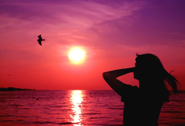 Silhouette of woman looking up to vivid purple pink colored sunrise sky with a flying bird
