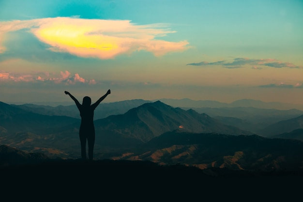 Silhouette of woman on mountain top over sky and sun light background,business, success, leadership, achievement and people concept