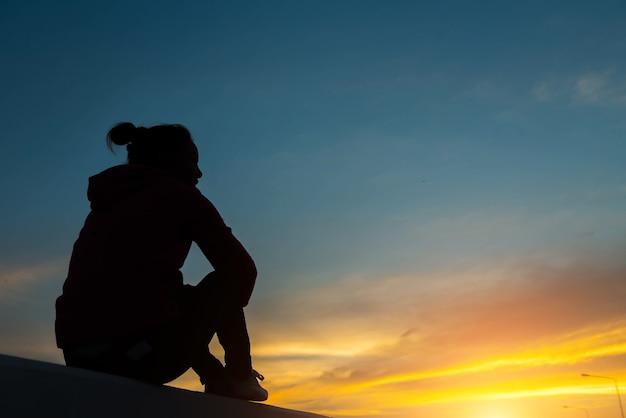 Силуэт женщины на дороге, наблюдая желтое и оранжевое заходящее солнце на закате