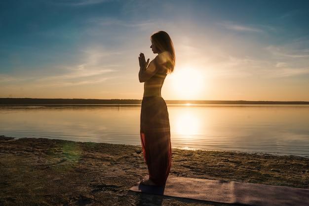 ヨガのアーサナをやって日没時にビーチでシルエットの女性。朝の自然ストレッチウォームアップトレーニング