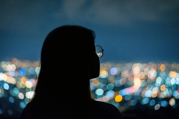 Silhouette woman portrait  in city night light bokeh  , chiang mai ,thailand