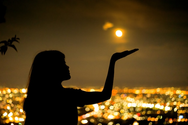 Silhouette woman portrait with full moon in city night light bokeh background