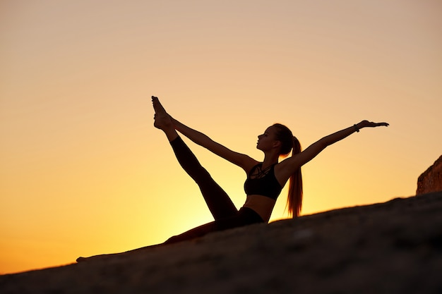 Silhouette woman practicing yoga or stretching at sunset or sunrise