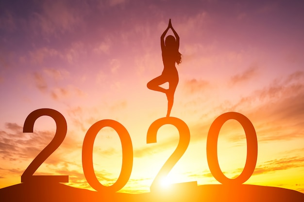 Silhouette of woman practicing yoga at sunrise with 2020