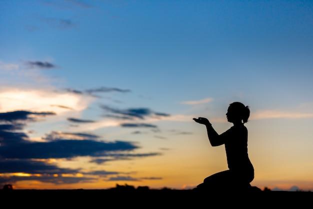 아름다운 하늘 배경 위에 기도하는 실루엣 여자