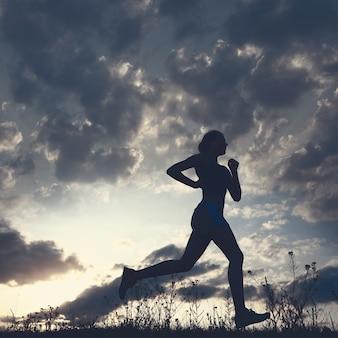 シルエットの女性は雲と太陽と青い空の下を走る