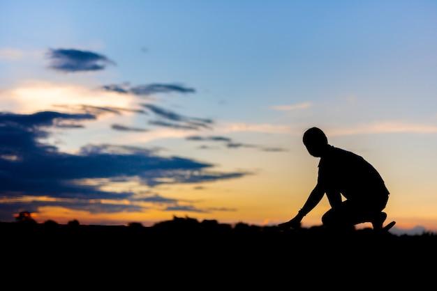 公園で美しい夕日に一人で走っているシルエットの女性。