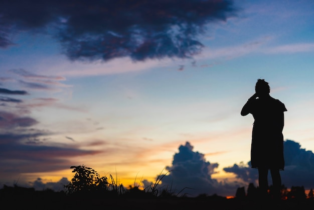 Silhouette woman sad standing at sunset