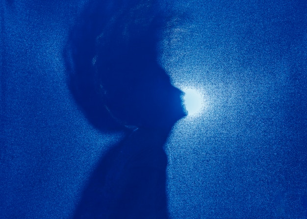 Silhouette of woman shaking hair