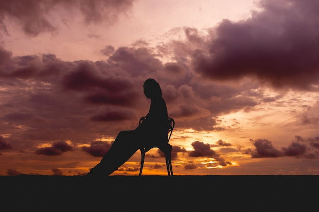 Silhouette of a woman sit on a chair with colorful dramatic sky.
