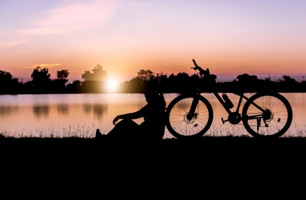 Silhouette woman sit near bicycle on sunset.