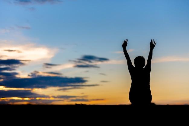 屋外の聖霊降臨祭の空をリラックスしたシルエットの女性の着席。