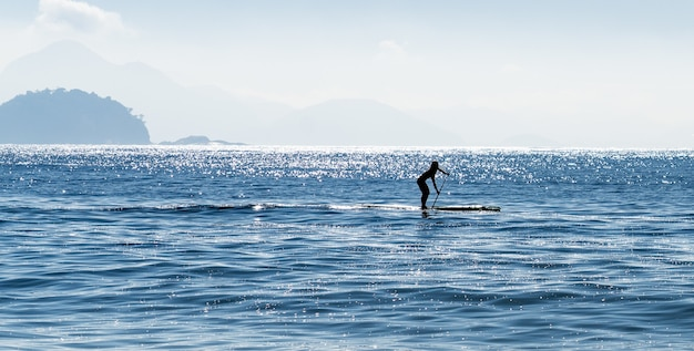 Silhouette of a woman stand up paddle surfing at the sea in brazil