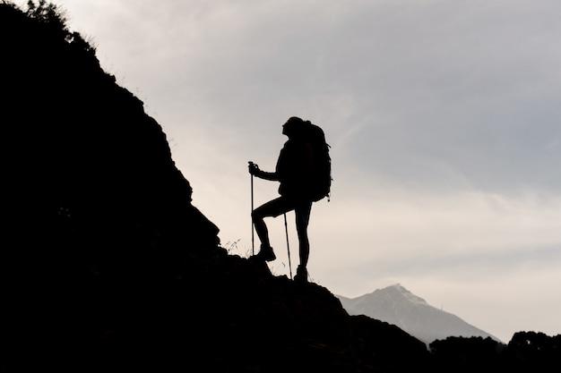 バックパックをハイキングし、杖を持つ岩の上に立っているシルエット女性