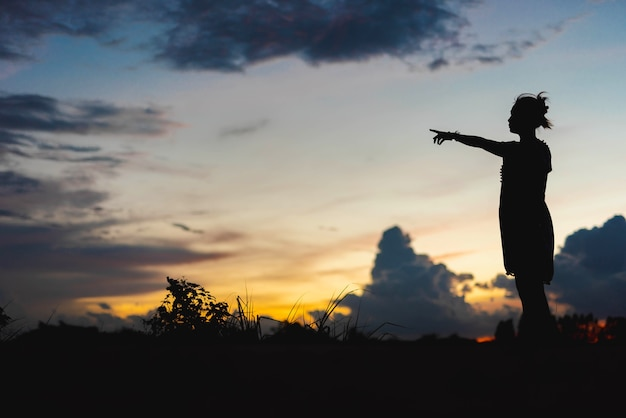 Silhouette woman standing pointing at sunset