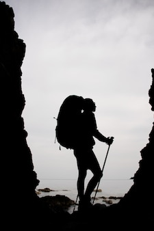 Silhouette woman standing between the rocks on the coastline on the sea with hiking backpack