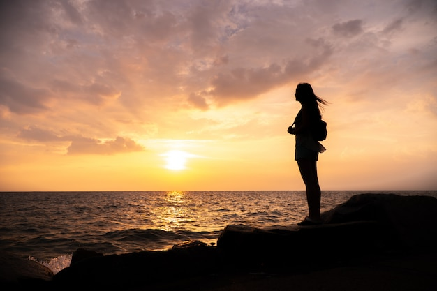 Silhouette woman standing, sunset sky over horizon.