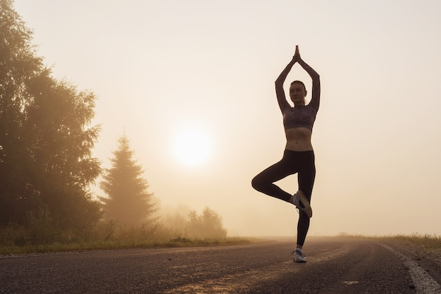 Silhouette of a woman at sunrise doing vrikshasana exercise near the edge of the road, tree pose