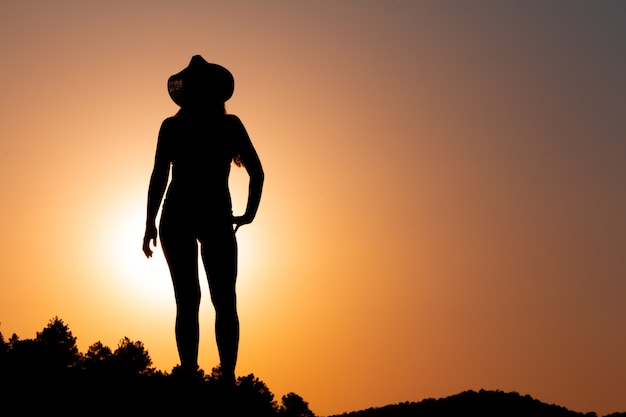 Silhouette of woman at sunset facing the sun wearing a hat concept of calm and serenity copy space