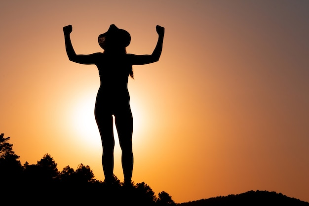 Silhouette of woman at sunset, facing the sun, wearing a hat. concept of strength and overcoming. selective focus.  overcoming problems. reaching a goal. copy space. self-confidence.
