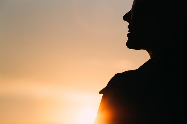 Silhouette of the woman at sunset
