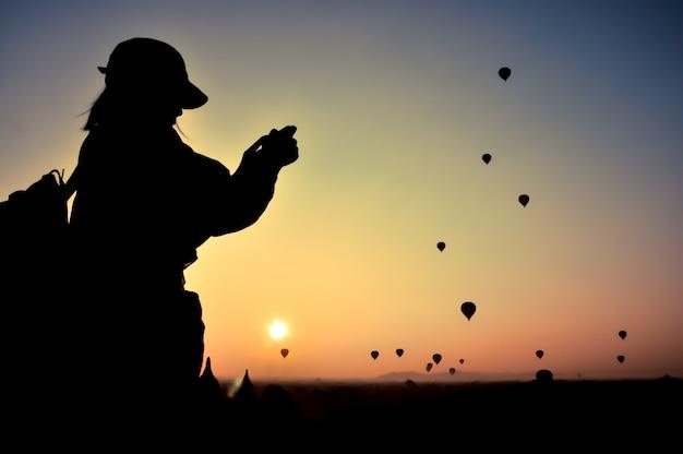 シルエットの女性旅行者は、ミャンマーのバガンの上にたくさんの熱気球で日の出の写真を撮ります。