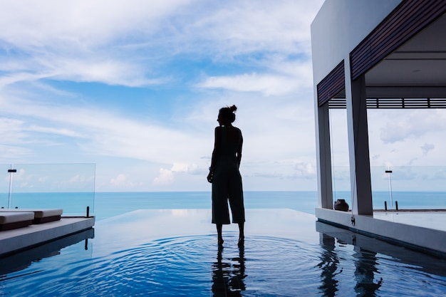 Silhouette of a woman walking on the water surface of the infinity pool of an expensive rich luxury villa on a mountain with a sea view