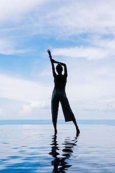 Siluetta di una donna che cammina sulla superficie dell'acqua della piscina a sfioro di una villa di lusso ricca costosa su una montagna con vista sul mare