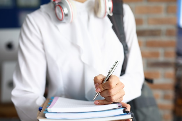 Silhouette of woman in a white shirt with headphones on her neck holds notebooks and pen