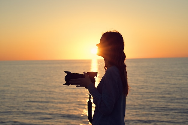 Silhouette of a woman with a camera at sunset near the sea side view. high quality photo Premium Photo