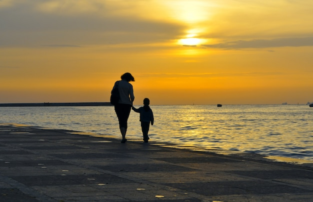 Silhouette of a woman with a child, they hold hands on a background of sea sunset