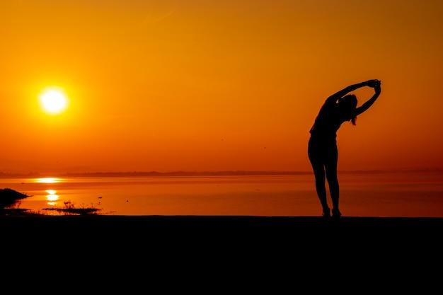 夕日を背景に一人でシルエットの女性のトレーニング。健康的で一人での運動活動。ウェルネスライフスタイルとアウトドアレクリエーション。