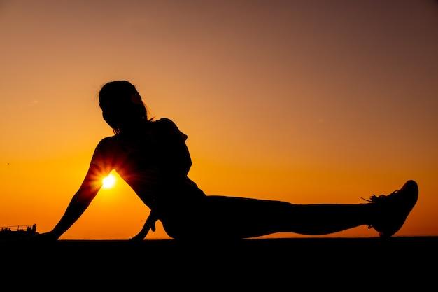 Тренировка женщины силуэта в одиночку с фоном заката. здоровая и сольная физическая активность. оздоровительный образ жизни и отдых на природе.