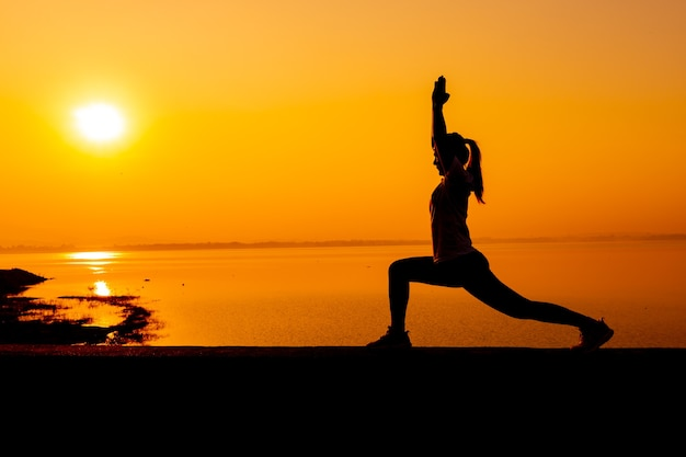 Silhouette woman workout alone with sunset background. healthy and solo exercise activity. wellness lifestyle and outdoor recreation.