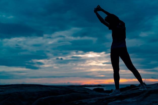 美しい日の出の空と石のビーチで午前中にシルエット女性トレーニング。トレーニングの前に体を伸ばして女性に合います。健康的なライフスタイルのための運動。戸外トレーニング。